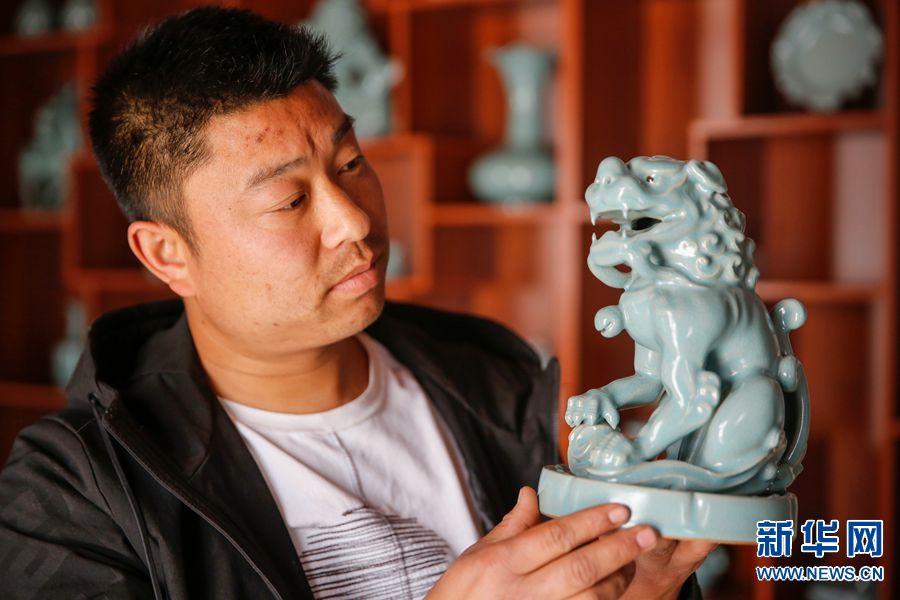 4月3日,河南省宝丰县大营镇清凉寺村艺人李淑杰在查看汝瓷作品狮子香薰炉。