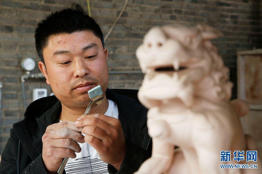 4月3日,河南省宝丰县大营镇清凉寺村艺人李淑杰在查看试烧片成色。