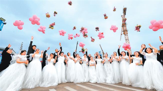 """4月26日,在""""五一""""国际劳动节即将到来之际,一场为建筑工友举办的集体婚礼在中建三局河南省科技馆新馆项目工地上演。当初因为经济等原因,这些建筑工友们举办的婚礼较为简朴,此次婚礼既圆了他们的梦想,又是对他们多年劳动奋斗的祝福与感谢。(记者 王铮 摄)"""