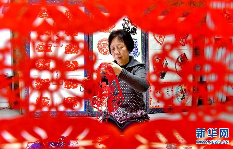 4月26日,洛宁剪纸市级传承人李彩霞,正在认认真真创作剪纸作品,她用小剪刀创作出一幅幅美轮美奂的作品。新华网发(高山岳 摄)
