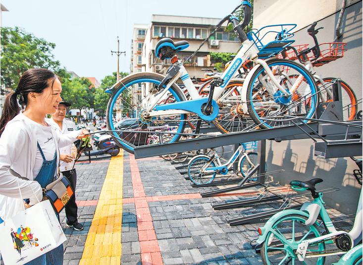 """7月9日,一双层共享单车立体""""停车器""""亮相郑州市中原区计划路街头,车架上整齐摆放着一排排共享单车,引来不少行人好奇的目光。现场附近竖立的使用说明牌显示,如要将共享单车放入该立体""""停车器"""",需将单个停车架整体拉出后垂直下压、将单车放入停车架上,抬起停车架至水平并前推至底部即可完成停车。据悉,该共享单车立体""""停车器""""长约20米,共2层,可同时供近百辆共享单车停放。辖区办事处工作人员介绍,该地段附近有家医院,人流密集,每天都有大量的共享单车被堆放在附近街道。街道管理方首次尝试安装了这种立体停车架,探索解决共享单车停车难问题。记者 王铮 摄"""
