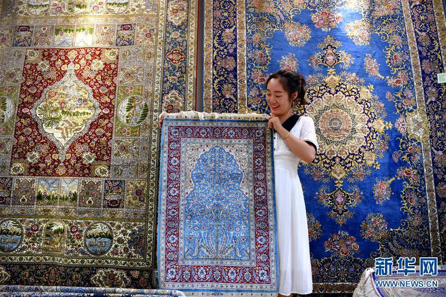 南阳宇翔工艺品有限公司的员工在展示制作好的真丝地毯(7月17日摄)。