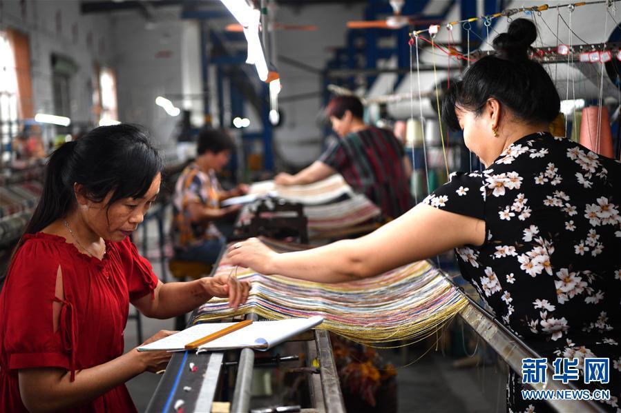 """南阳宇翔工艺品有限公司的员工在车间编织真丝地毯(7月17日摄)。   近年来,河南省南召县依托传统柞蚕养殖业,着力发展真丝地毯编织特色产业,并积极探索""""企业+农户""""生产模式。南召真丝地毯主打波斯风格,图案精美,做工细腻,远销俄罗斯、伊朗等30多个国家和地区,为带动当地经济发展、群众农闲增收起到了积极作用。新华社记者 李嘉南 摄"""