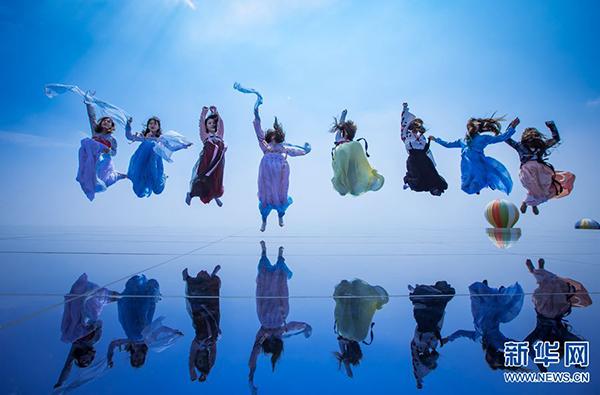 """9月9日,女游客们着汉服在河南新密""""天空之镜""""拍摄美照,尽显梦幻浪漫。据悉,当日郑州版""""天空之镜""""在河南新密伏羲山惊艳亮相。从低处仰拍,这些穿着汉服的女孩儿,在""""天空之镜""""上翩翩起舞,有种空明澄澈的感觉,仿佛置身于""""水天一色""""之中,梦幻浪漫。据了解,这处""""天空之境""""位于伏羲山红石林山顶,由56块双层钢化玻璃组成,近200平方米。新华网 张为涛 摄"""