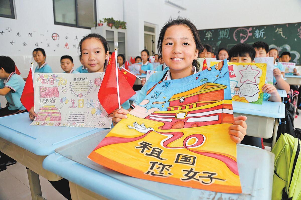 """9月25日,焦作市解放区映湖路小学五年级学生在展示自己创作的""""祖国您好""""主题手抄报,以实际行动向新中国成立70周年献礼。(李良贵 摄)"""