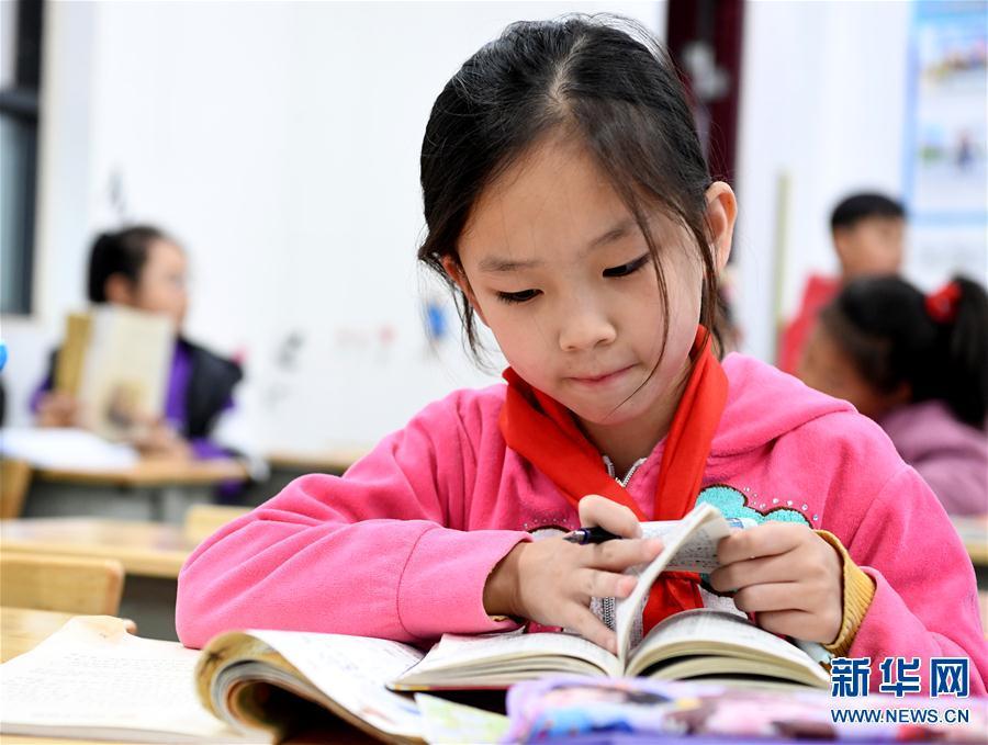 """10月15日,新乡市育才小学明德校区的学生在课后写作业。 自2019年3月起,河南省新乡市在中小学开展""""四点半课堂""""活动。下午放学后,学校组织教师对有留校需求的学生进行课业及艺术、科学等方面的辅导,满足学生课后学习及兴趣爱好的需求。""""四点半课堂""""为学生提供了一个学习休闲的好去处,深受学生及家长欢迎。新华社发(郝源 摄)"""