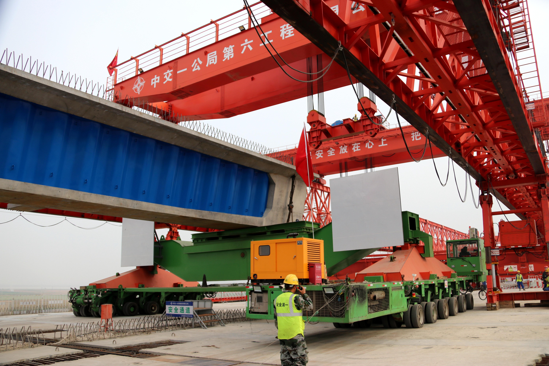 ▲大型运梁机在向大型架桥机吊位运梁