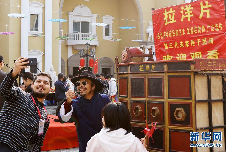 """11月4日,以""""盛世中国,多彩世界""""为主题的郑州西亚斯学院第二十一届国际文化节精彩开幕。在持续一周的文化节期间,将先后举行""""中国日""""""""亚洲日""""""""欧洲日""""及独具特色的""""国际日""""活动,既有""""歌、舞、戏、琴、茶""""的视听盛宴,又有来自世界各地的风味美食;有特色鲜明的民族传统文化体验,更有高层次、高水平的中外专家、学者学术讲座活动,还增设""""2019国际教育展"""",让中外师生足不出校门也可享受到一场国际化的视听盛宴。在""""中国日""""的文化欣赏活动中,非物质文化遗产项目展示、中国传统民间艺术""""拉洋片""""""""剪影""""""""传统纺织""""""""艺术烙画""""""""传统糖人糖画""""等令师生大饱眼福,少林拳、太极拳表演也让观众拍手叫绝。新华网发(左倩肖胜春摄)"""