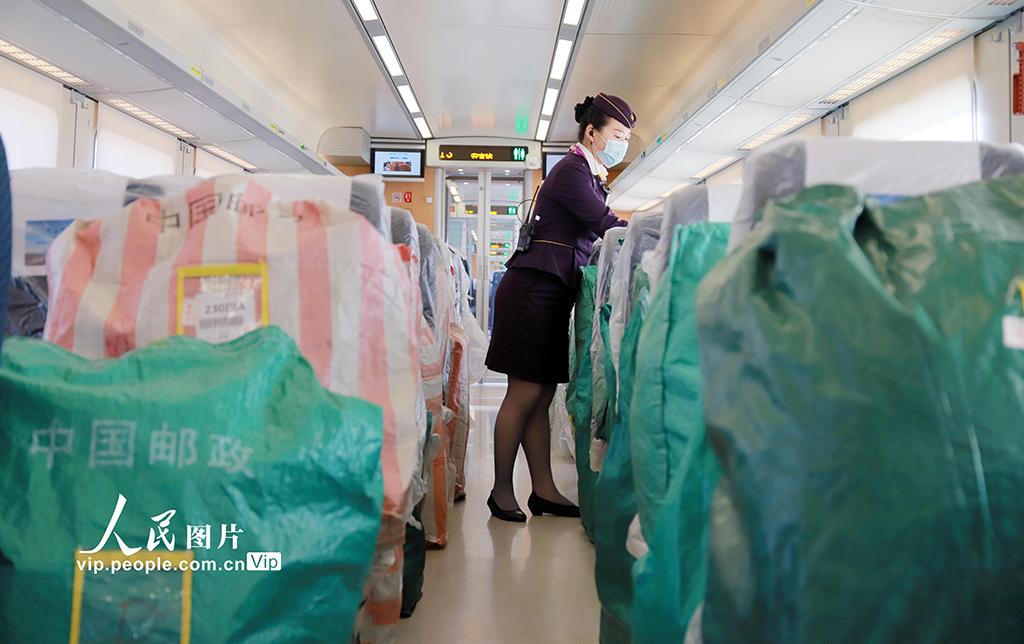 """2020年11月12日,杭州东站,铁路工作人员将快件装运到开往成都东的D2262次列车上。随着各大电商平台提前抢跑""""双11""""旺季,销售周期的拉长,带来包裹快递量持续增长。为适应新发展格局下的物流市场需求,铁路部门自11月1日起启动""""双11""""电商黄金周运输服务,持续至11月20日,运输期限较往年10天延长为20天。周围 人民图片"""