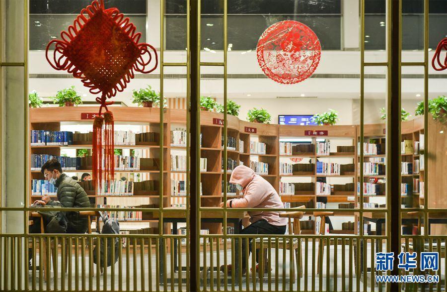 """2021年1月10日晚,市民在洛阳市洛龙区宜人坊""""河洛书苑""""城市书房内看书,享受冬日里的书香温暖。近年来,河南省洛阳市加快构建文化传承创新体系,深入实施文化惠民工程,着力推动全民阅读,打造""""15分钟阅读圈"""",把城市书房建设列入重点民生实事。截至目前,洛阳市全市已建成对公众免费开放的""""河洛书苑""""城市书房200余座,为居民在家门口休闲阅读提供了便利条件。新华网发(黄政伟 摄)"""